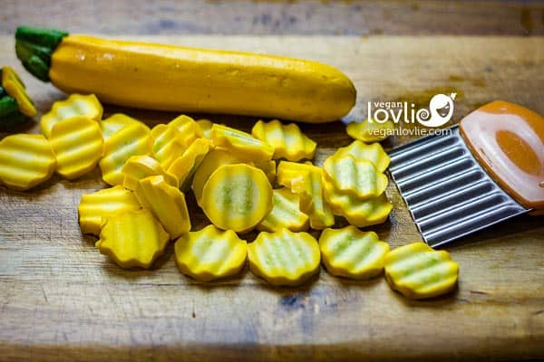 Cutting yellow zucchini on chopping board with a crinkle cutter